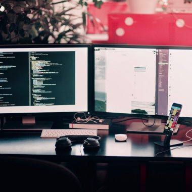 A photo showing some coding on two monitors. Adding an XML File to a C# project is easy.