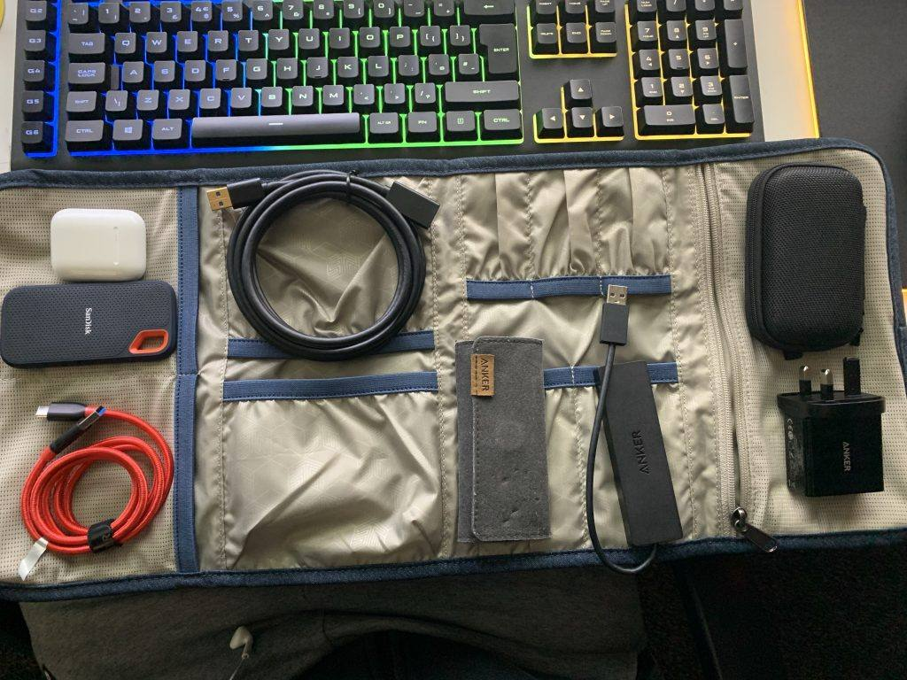 This image shows the STM Wrapper Dapper storage pouch with cables and accessories on top.